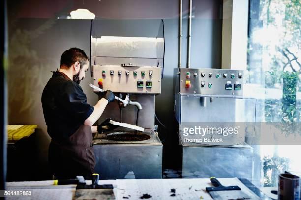 Chocolatier creating chocolates in mold in kitchen