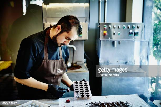 chocolatier examining hand made chocolates in shop - chocolate making stock pictures, royalty-free photos & images