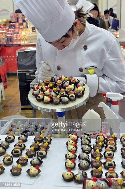 A chocolatier of Japanese sweet shop Goncharoff puts the finishing touches to animalshaped chocolates at Tokyo's Takashimaya department store on...