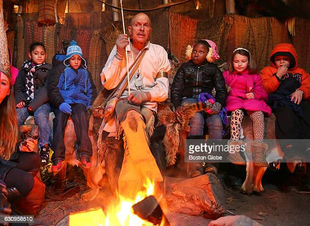 Choctaw Indian Jon Rice tells stories to children sitting around his fire inside a wetu at the Wampanoag Homesite at Plimoth Plantation in Plymouth...
