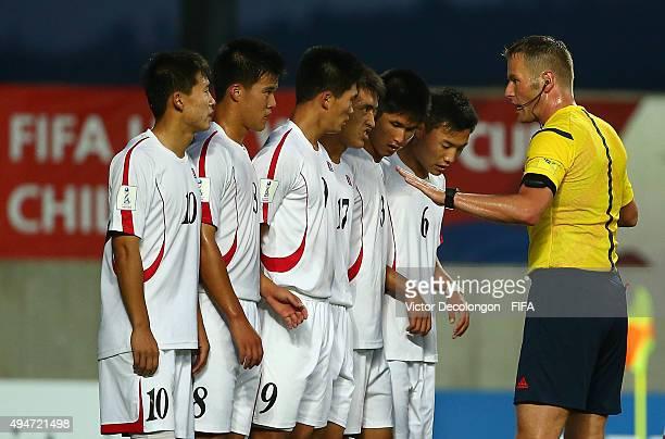 Choe Song Hyok Yon Jun Hyok Han Kwang Song Jang Song Il Kim Wi Song and Kim Ye Bom of Korea DPR listen as FIFA referee Danny Makkelie gives...