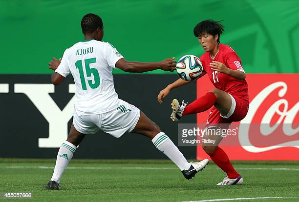 Choe Un Hwa of Korea DPR and Ugo Njoku of Nigeria in action during the FIFA U20 Women's World Cup Canada 2014 Semi Final match between Korea DPR and...