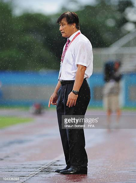 Choi Duck Joo coach of South Korea stands out in the rain during the FIFA U17 Women's World Cup Semi Final match between South Korea and Spain at the...