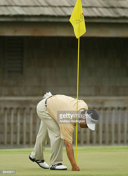 J Choi of Korea retrieves his ball from the hole after holing out for eagle on the 11th hole during the final round of the Masters at the Augusta...