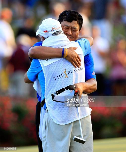 J Choi of South Korea celebrates with caddie Andy Prodger after making a parsaving putt to defeat David Toms on the first playoff hole to win THE...