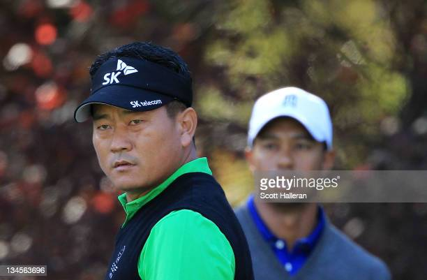 Choi of South Korea watches his tee shot on the second hole as Tiger Woods looks onduring the second round of the Chevron World Challenge at Sherwood...