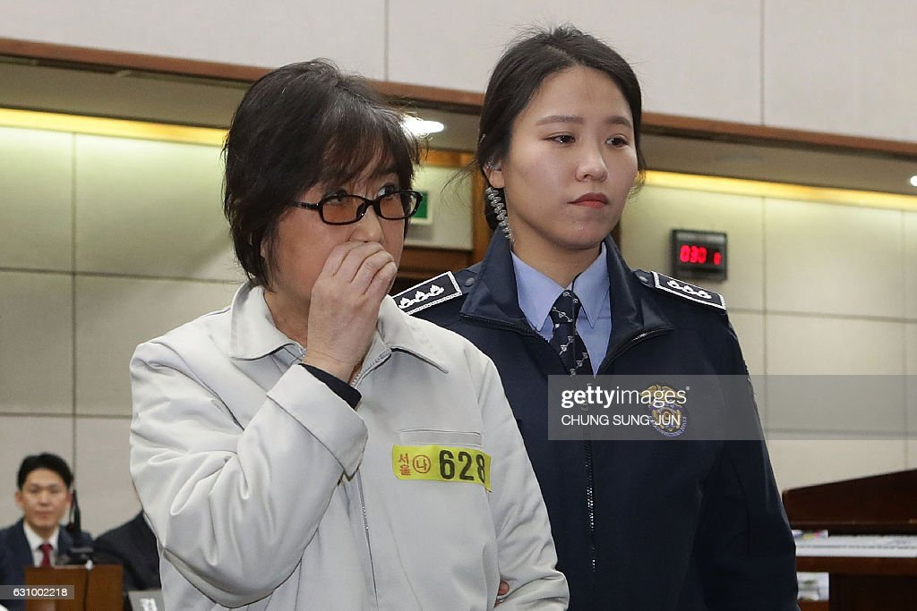 Choi Soon-Sil (L), the jailed confidante of disgraced South Korean President Park Geun-Hye, appears on the first day of her trial at the Seoul Central District Court in Seoul on January 5, 2017. Choi, the woman at the centre of a corruption scandal that triggered the biggest political crisis for a generation in South Korea, appeared in court on January 5 on fraud charges. / AFP / POOL / Chung Sung-Jun