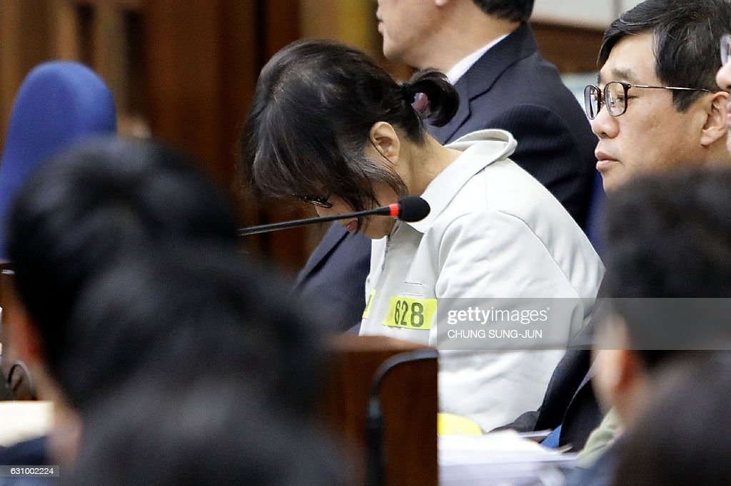 Choi Soon-Sil (C), the jailed confidante of disgraced South Korean President Park Geun-Hye, sits in the courtroom as she appears on the first day of her trial at the Seoul Central District Court in Seoul on January 5, 2017. Choi, the woman at the centre of a corruption scandal that triggered the biggest political crisis for a generation in South Korea, appeared in court on January 5 on fraud charges. / AFP / POOL / Chung Sung-Jun