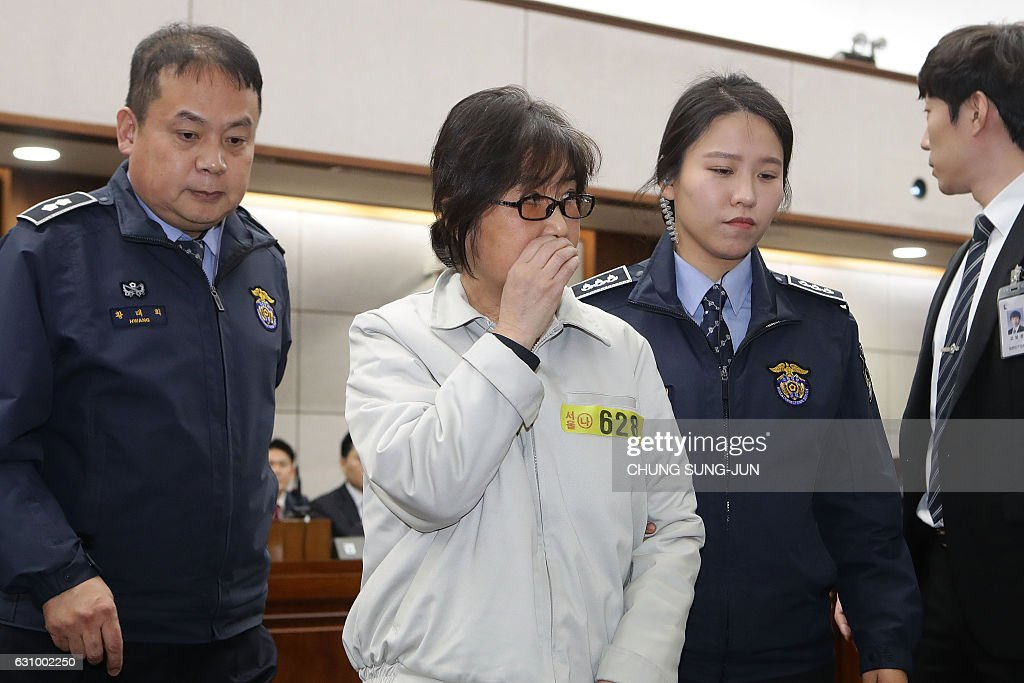 Choi Soon-Sil (C), the jailed confidante of disgraced South Korean President Park Geun-Hye, appears on the first day of her trial at the Seoul Central District Court in Seoul on January 5, 2017. Choi, the woman at the centre of a corruption scandal that triggered the biggest political crisis for a generation in South Korea, appeared in court on January 5 on fraud charges. / AFP / POOL / Chung Sung-Jun