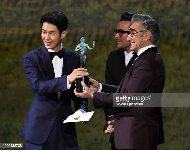 Choi Wooshik accepts Outstanding Performance by a Cast in a Motion Picture for 'Parasite' from Dan Levy and Eugene Levy onstage during the 26th...