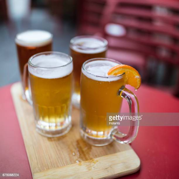 a choice of four refreshing beers on the red table of a pub patio: apricot beer, ipa, cream ale and lager. - help:ipa stock pictures, royalty-free photos & images