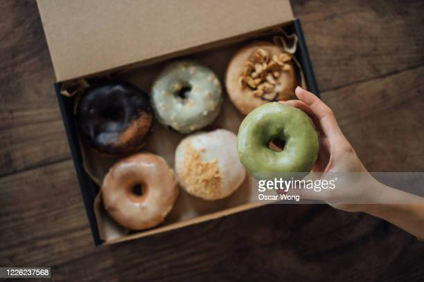 a choice of various delicious crafted donuts from a takeaway box - elevated view stock pictures, royalty-free photos & images