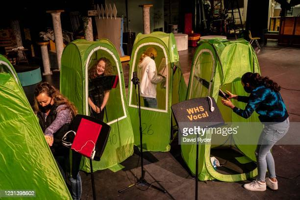 Choir director Dawn McCorkmick and students Emma Banker, Jessi McIrvin, and Valerie Sanchez prepare pop-up tents during choir class at Wenatchee High...