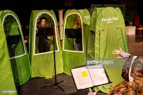 Choir director Dawn McCormick leads students as they record vocals in pop-up tents during choir class at Wenatchee High School on February 26, 2021...