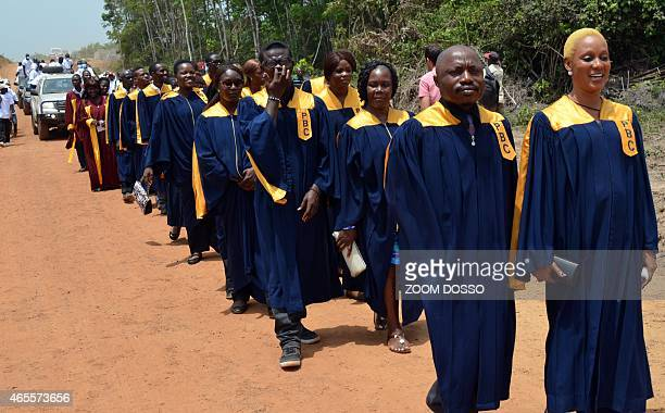 A choir group sings ahead of the car transporting the remains of the Ebola victims on March 7 2015 in Monrovia 16 barrels containing the remains of...