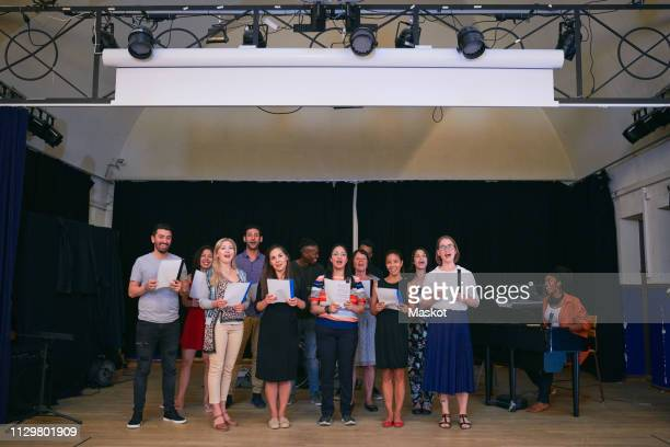 choir members performing on stage in school auditorium - rehearsal stock pictures, royalty-free photos & images