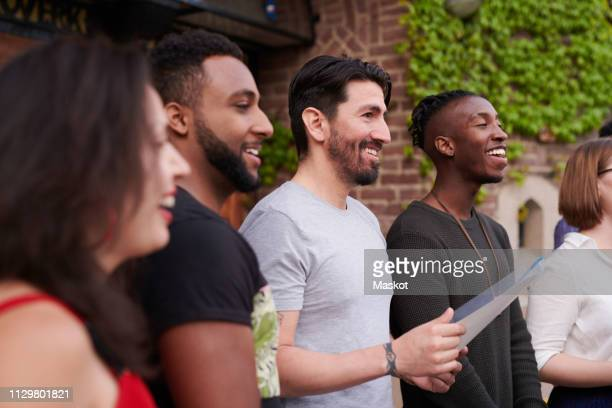 choir singers with music sheet singing outside language school - choir stock pictures, royalty-free photos & images