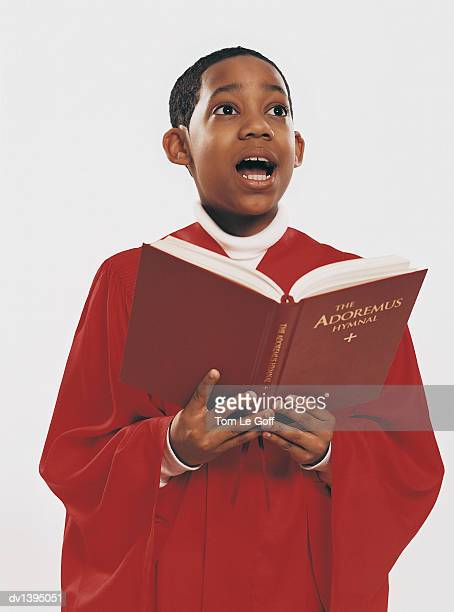 choirboy in a red gown singing from a hymn book - choir stock pictures, royalty-free photos & images