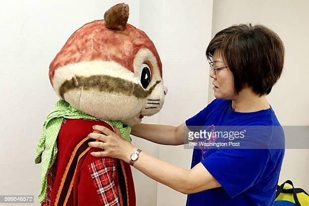 Choko Ohira, who runs the Mascot Actors School, helpsYukoMura with her squirrel costume. Mura, who is 19,started at the school in January this...