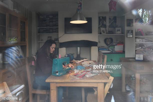 Chole Newman uses a sewing machine to make personal protective equipment for NHS staff at her home in Tenterden, south east England, on April 17,...