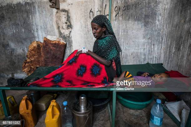 A cholerastricken woman with her baby in a former prison in Wajid Somalia Somalia is in the grip of an intense drought induced by consecutive seasons...