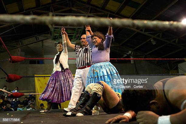 Cholita wrestlers Yolanda La Amorosa and her tag team mate Carman Rosa celebrate victory over their male counterparts during the 'Titans of the Ring'...