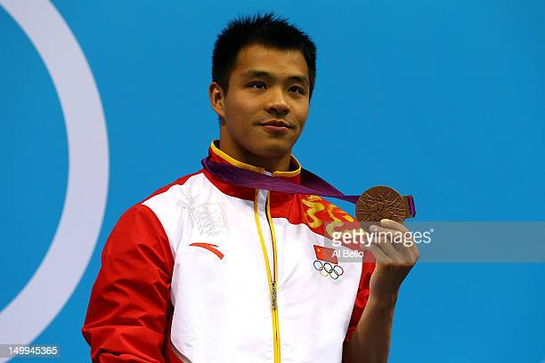 Chong He of China poses on the podium during the medal ceremony for the Men's 3m Springboard Diving Final on Day 11 of the London 2012 Olympic Games...