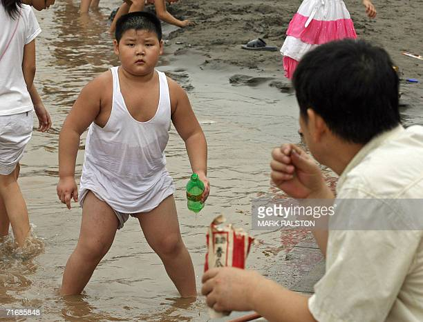 An young overweight boy known locally as a 'Little Emporer' plays by the Yangtze river in Chongqing 21 August 2006 China is sounding the alarm bell...