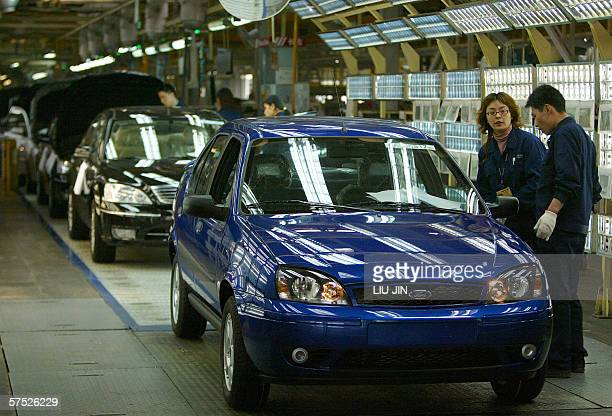 Workers take the final inspection on a Ford car on the production line at the Changan Ford plant in China's southwestern city of Chongqing 27 March...