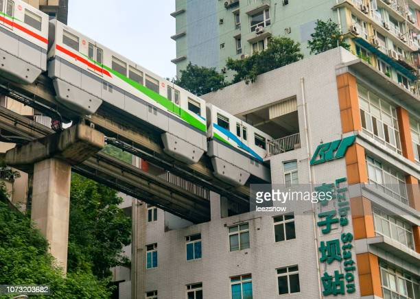 chongqing monorail entering apartment building - chongqing stock photos and pictures
