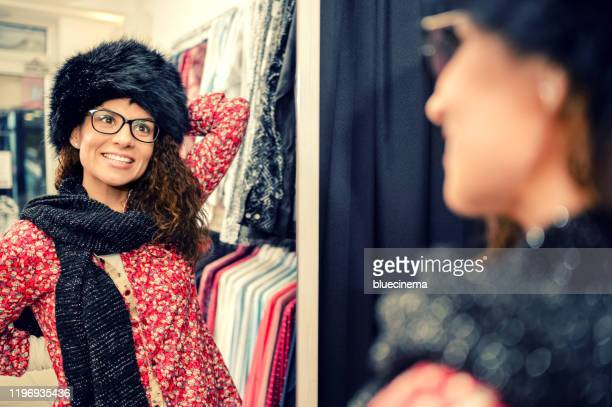 choosing a fur hat - fur hat stock pictures, royalty-free photos & images