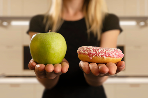 Choosing Between Donut And Apple 1007305478