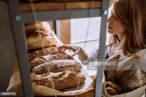 het kiezen van vers brood voor haar klanten - handwerkprodukten stockfoto's en -beelden