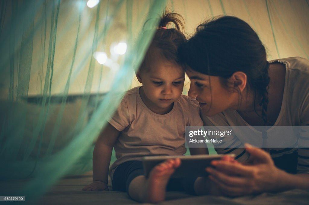 Choosing her favourite bedtime ebook : Stock Photo