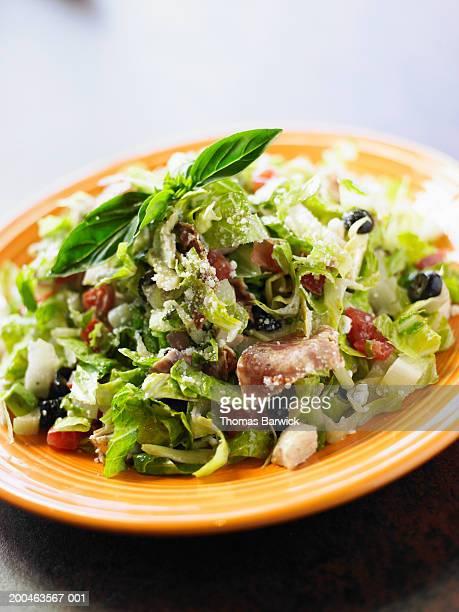 Chop salad with croutons, salami, black olives, parmesan and basil