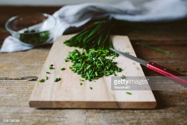 chopped and whole chives and kitchen knife on wooden board - チャイブ ストックフォトと画像