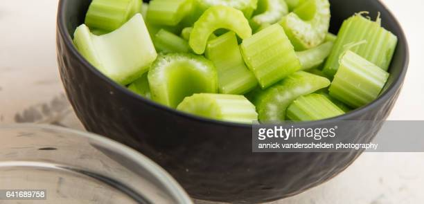 Chopped celery in black bowl.