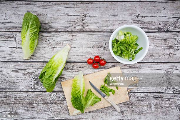 Chopped romaine lettuce and kitchen knife wooden board