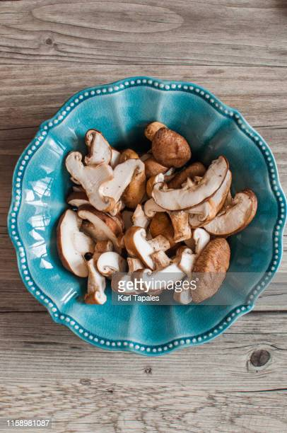 chopped shiitake mushrooms on a rustic wooden table - shiitake mushroom stock pictures, royalty-free photos & images