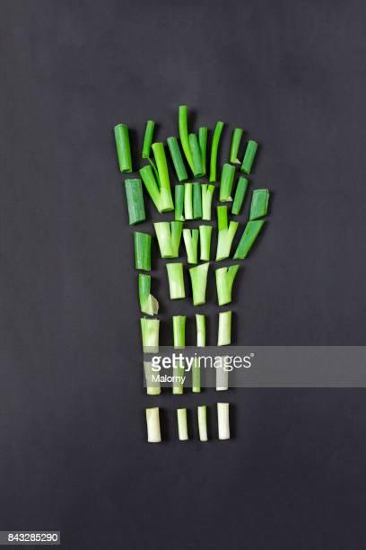 chopped spring onions on black background. greenery - cipollina foto e immagini stock