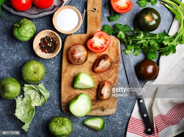 Chopped tomatoes and knife on cutting board fresh vegetables on the table top view