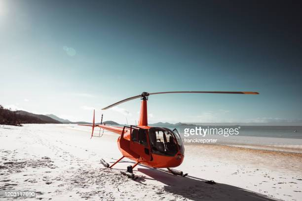 chopper parked on whitsunday beach in australia - helicopter stock pictures, royalty-free photos & images