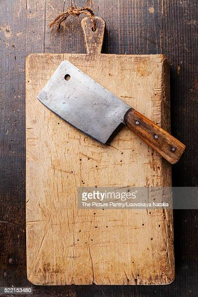 Chopping board and Meat cleaver on dark wooden background