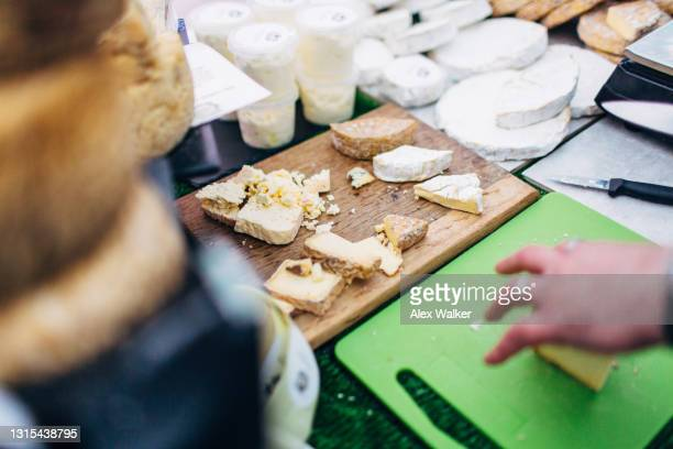 chopping board with various cheeses in market stall - french culture stock pictures, royalty-free photos & images