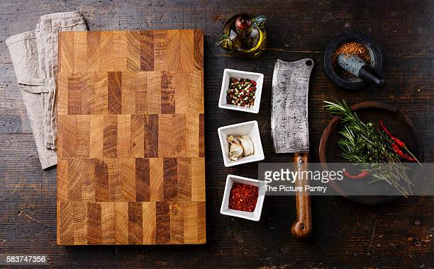 Chopping cutting kitchen board, seasoning, herbs and Butcher meat cleaver on dark wooden background