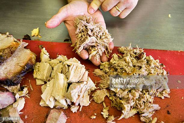 Chopping is the preferred way to prepare pork shoulder meat rather than using a machine where it comes out stringy and mushy shown by the meat being...