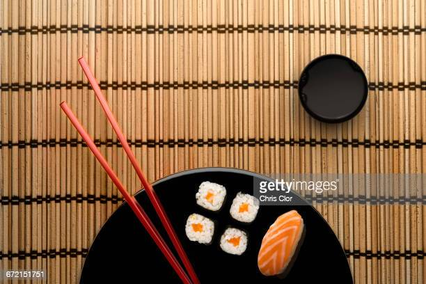 chopsticks and sushi on round plate with dipping sauce - soy sauce stock photos and pictures
