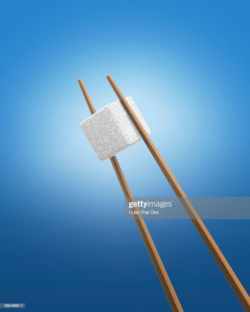 Chopsticks holding a white sugar cube : Stock Photo