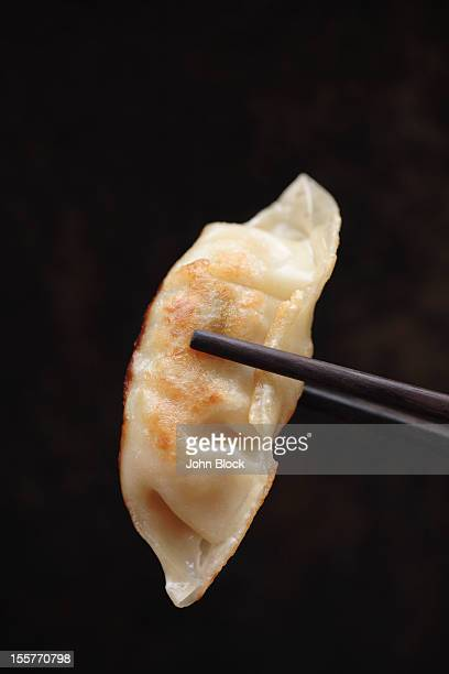Chopsticks holding Asian dumpling
