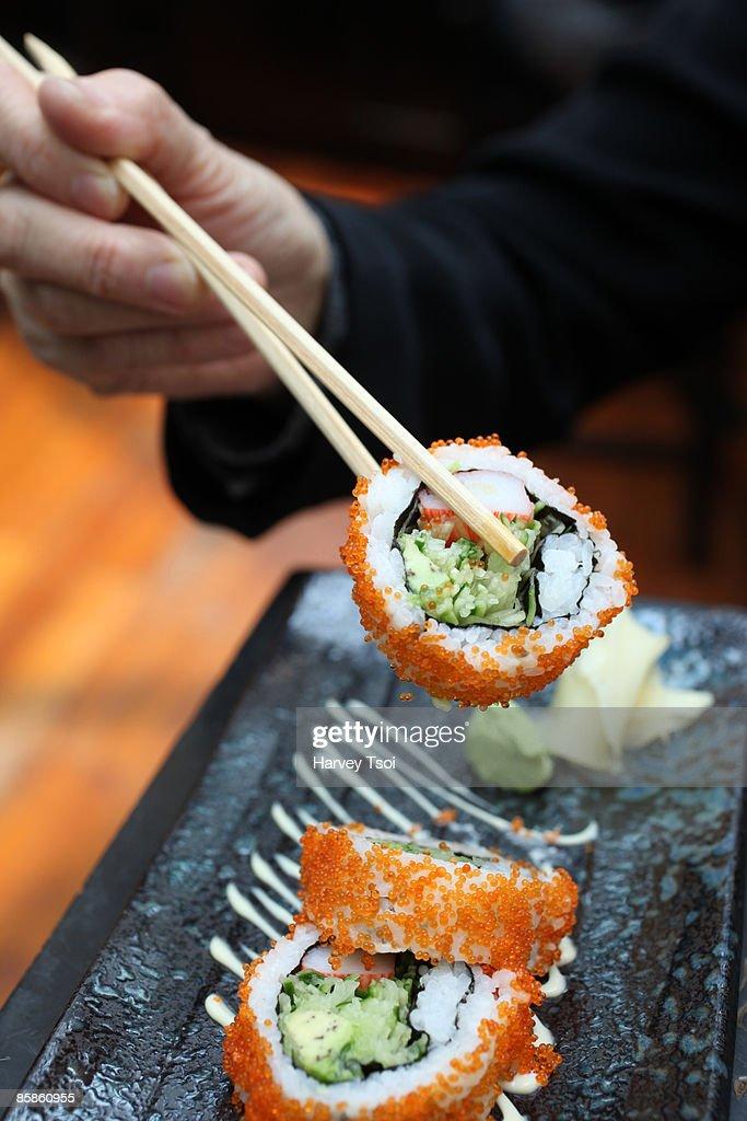 Chopsticks Holding Sushi : Stock-Foto